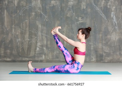 Young woman practicing yoga on grey background