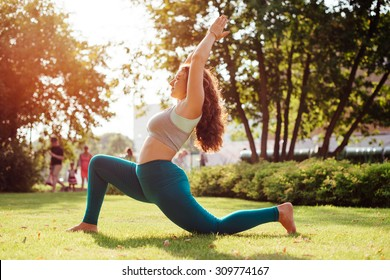 Young woman practicing yoga outdoor in park. Toned picture