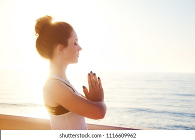 Young woman practicing yoga outdoors by the sea at sunset. Girl standing with eyes closed and prayer hands. Female portrait in profile