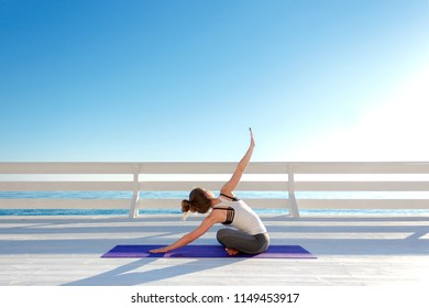 Young woman practicing yoga outdoors at white wooden seafront. Sitting in easy pose and bending forward, twistinf with arms wide open.