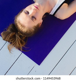 Young woman practicing yoga outdoors. Girl in shavasana on purple mat on white wooden floor. Overhead sport close up