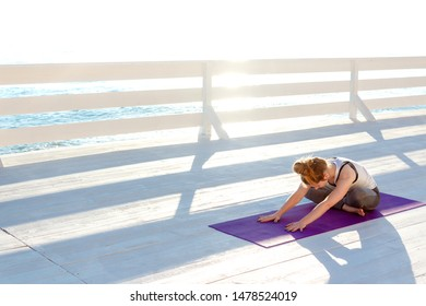 Young woman practicing yoga outdoors at white wooden seafront. Sitting in easy pose and bending forward for stretching