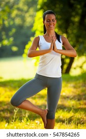 Young woman is practicing yoga outdoors in the nature.