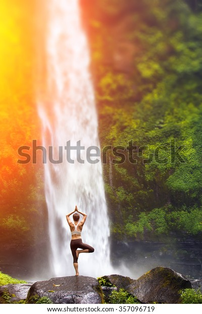 A young woman practicing yoga outdoors in front of the beautiful waterfall.