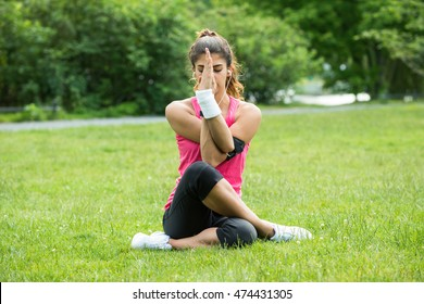 Young Woman Practicing Yoga In Park On Summer Day