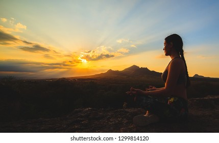 Young woman practicing yoga or pilates at sunset or sunrise in beautiful mountain location
