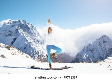 Young woman practicing yoga pose outdoors in winter. Stretching workout in snow on top of mountain. Hiking in cold season. Calm and silent view.