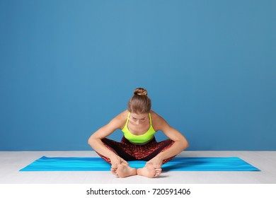 Young woman practicing yoga pose near color wall indoors