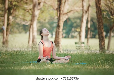 Young woman practicing yoga poses on the garden