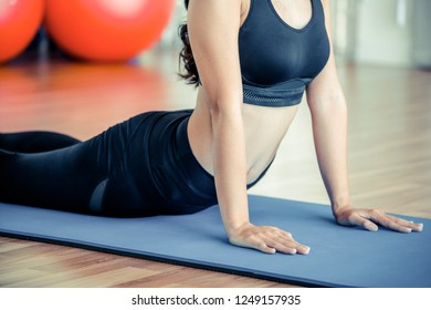 Young woman practicing yoga position in an indoor gym studio. Healthy and wellness lifestyle concept.