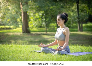 Young woman practicing yoga in the public garden