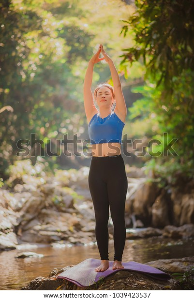 Young woman practicing yoga in rear view, waterfall