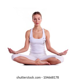Young woman practicing yoga, sitting in a lotus position, isolated over white