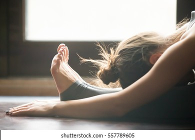 Young woman practicing yoga, sitting in Seated forward bend exercise, paschimottanasana pose, working out, wearing sportswear, grey pants, bra, indoor, home interior background, close up