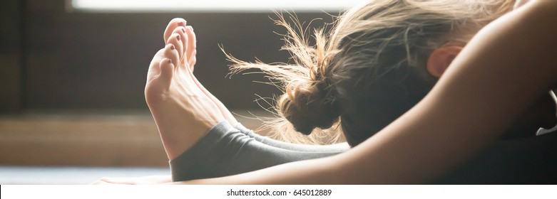 Young woman practicing yoga, sitting in Seated forward bend exercise, paschimottanasana pose, indoor, home interior background, close up. Horizontal photo banner for website header design