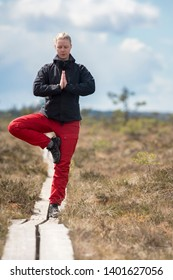 Young Woman practicing Yoga standing tree pose (Vrikshasana) outdoor in nature with wildlife clothing in wide open landscape background - Horizontal photograph.