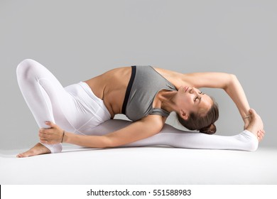 Young woman practicing yoga, stretching in Revolved Head to Knee Forward Bend exercise, Parivrtta Janu Sirsasana pose, working out wearing sportswear, indoor full length, grey studio background