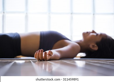 Young woman practicing in a yoga studio. Shavasana or corps pose is the end of a class or practice.