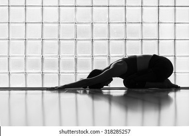 Young woman practicing in a yoga studio. Child pose, resting pose.