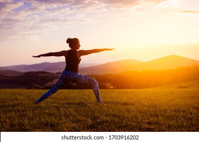 Young woman practicing yoga with sunset in nature
