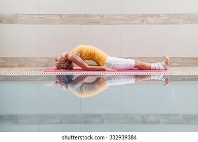 Young woman practicing yoga at swimming pool, Matsyasana / Fish pose