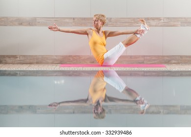 Young woman practicing yoga at swimming pool, Navasana / Variation of Boat pose