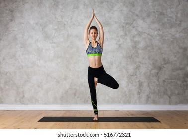 Young woman practicing yoga Tree pose, Vrikshasana against texturized wall / urban background