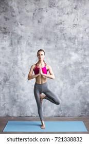 Young woman practicing yoga Tree pose, Vrikshasana in gym. Yoga concept.
