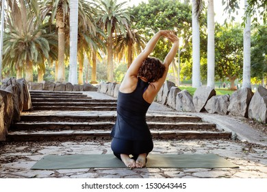 Young woman practicing yoga in tropical park. Vajrasana or Thunderbolt  asana  toned background. Copy space.  Healthy lifestyle and doing exercises concept.