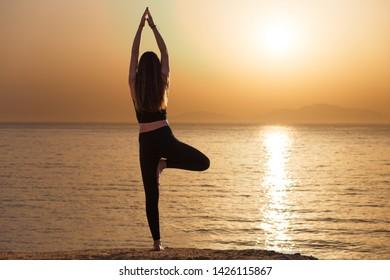 Young woman practicing yoga vrikshasana pose in the morning at the sea