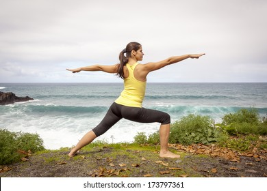Young woman practicing yoga warrior pose near the ocean