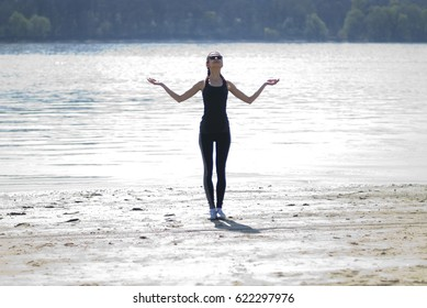 Young woman practises exercise by the river