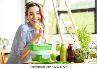 Young woman prapairing food in green lunch boxes sitting on the table indoors