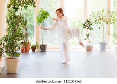 Young Woman praticing tai chi chuan in the gym. Chinese management skill Qi's energy.