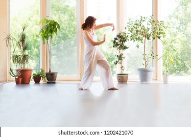Young Woman praticing tai chi chuan in the home. Chinese management skill Qi's energy.