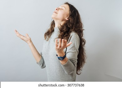 Young woman prayed to God hands upward. On a gray background.