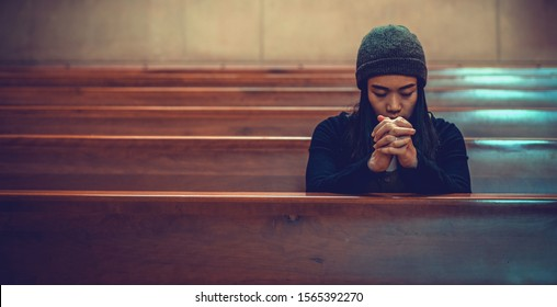 Young woman prayer's pray alone in church, People pray to God with folded hands, old wooden classic long chairs background