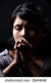 Young woman is in praying against dark background