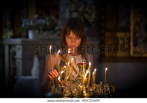 A young woman praying in a church
