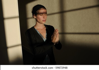 Young woman praying with closed eyes in little church.