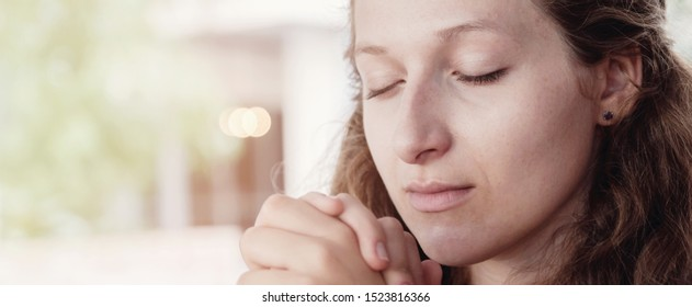 Young woman praying with eyes closed, World Day of Prayer,international day of prayer