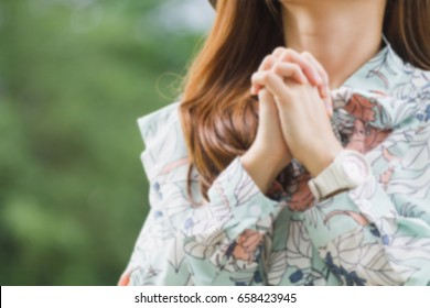 A young woman praying for God's blessing.