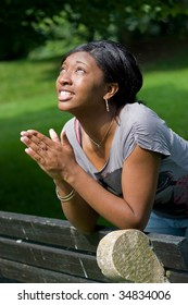 A young woman praying with her hands together.