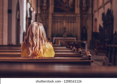 Young woman praying and meditating in church. Belief in Jesus Christ. Catholic cathedral with symbol of religion