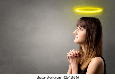 Young woman praying on a grey background with a shiny yellow halo above her head