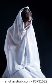 Young woman praying on his knees on a dark background.