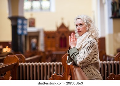young woman praying in quite church