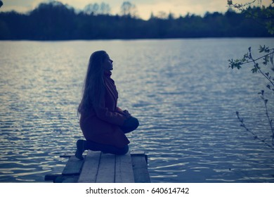 Young woman prays silhouette on the lake dock