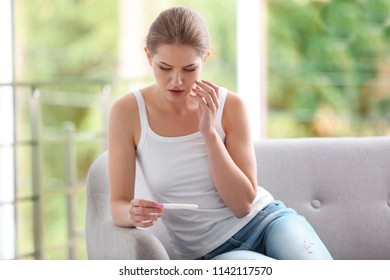 Young woman with pregnancy test at home. Gynecology