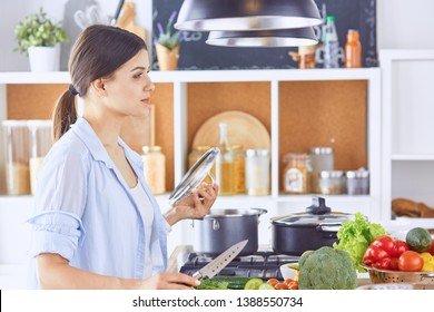 A young woman prepares food in the kitchen. Healthy food - vege
